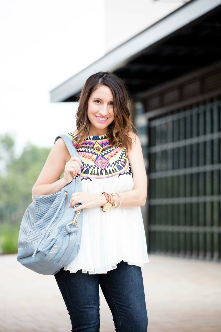 Bright spring top, skinny jeans, and light blue hand bag