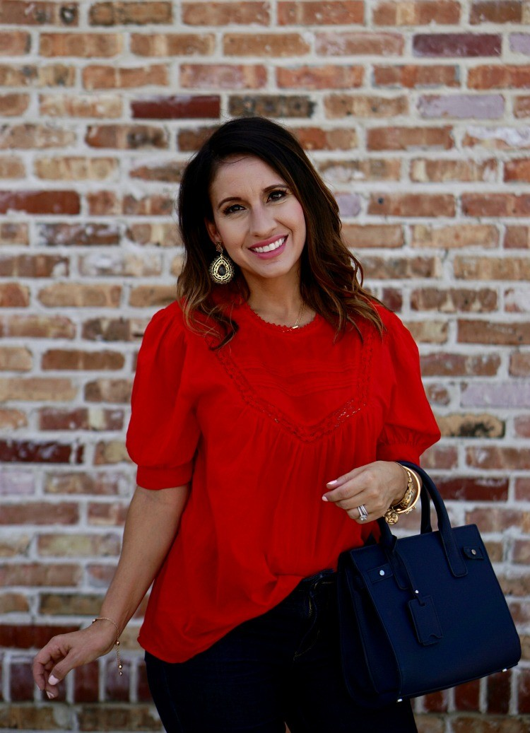 Statement earrings, red top, and dark skinny jeans