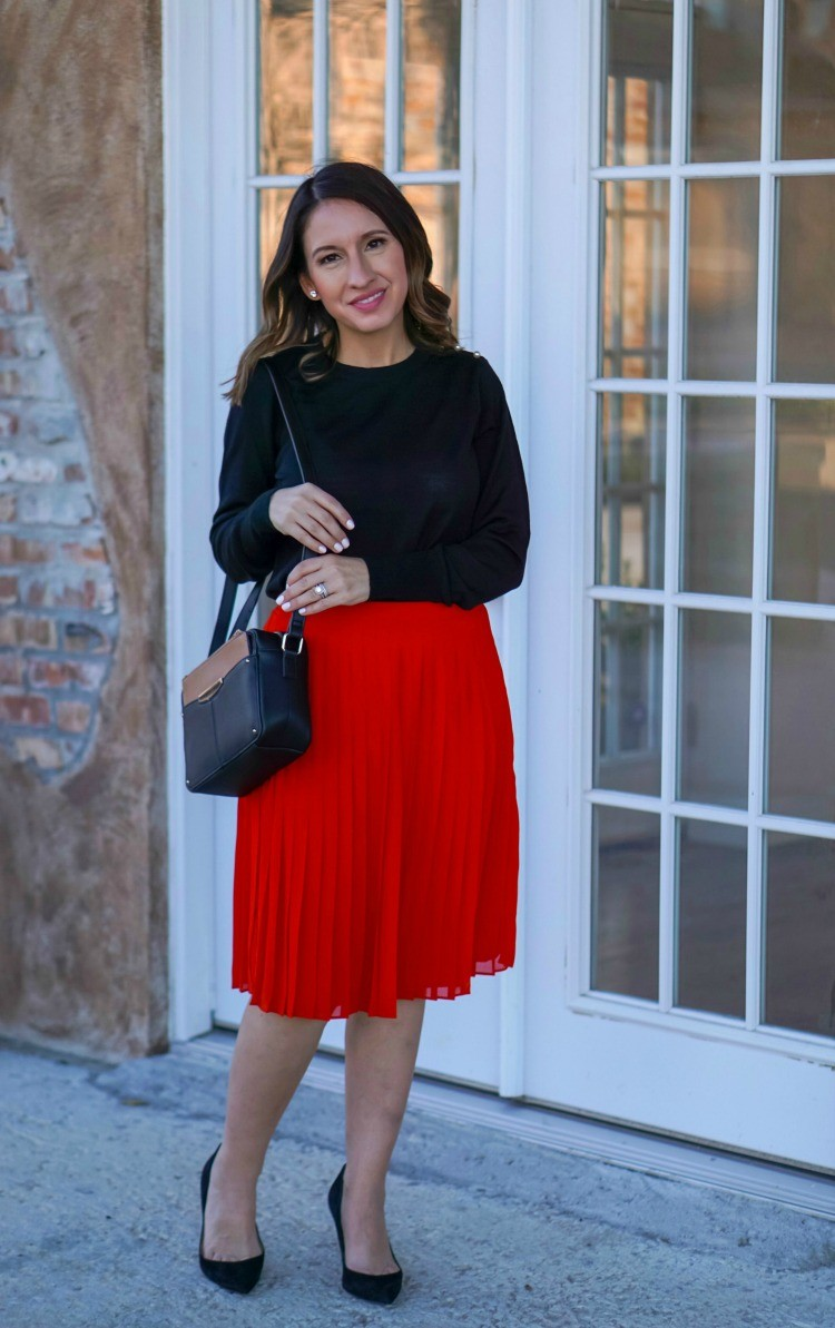 Black sweater, red pleated skirt, and heels