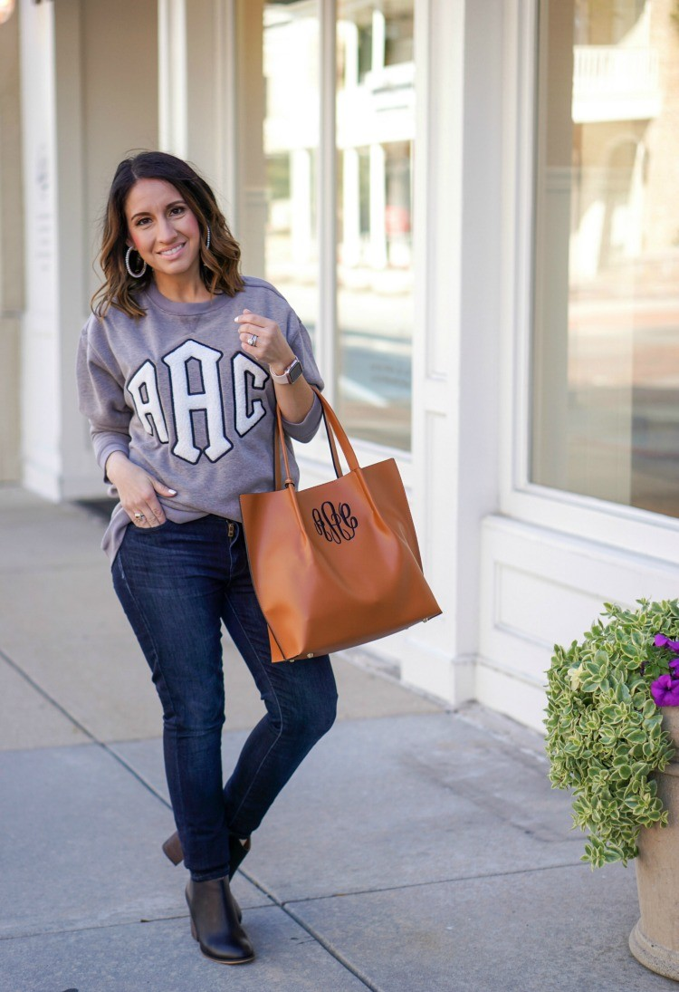 Marley Lilly Letterman Sweatshirt, Monogrammed tote, dark denim, black booties, and pearl hoops