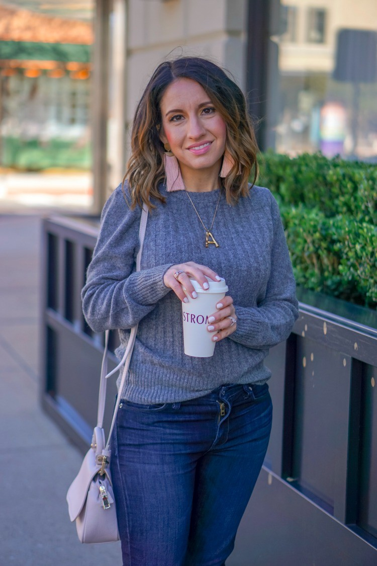 Statement earrings, ribbed sweater, and jeans
