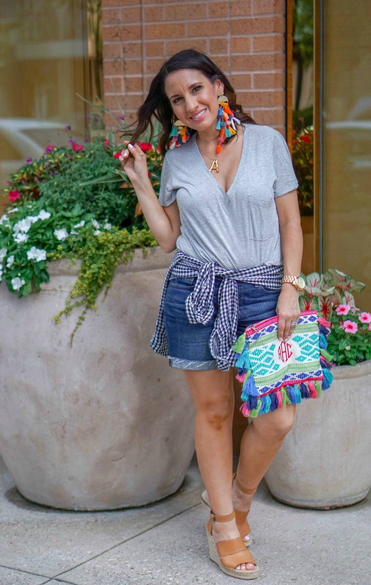 Statement earrings, grey tee, denim shorts, wedges, and MarleyLilly clutch